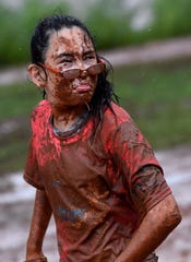 Abigail Hamilton, 13, spits mud and grass out of her mouth, still wearing her glasses though she admitted she couldn't see out of them during the Mudslinger Fun Run.