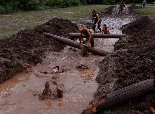 Runners crawl and fall in the mud of a pit near the end of Saturday's Mudslinger Fun Run.