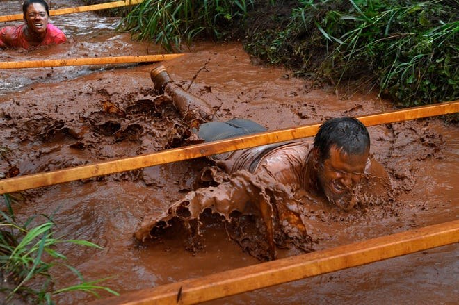 D.J. Davidson laughs as he lifts his head from the mud after diving beneath an obstacle. Behind him, his wife Stephanie follows. The eighth annualMudslinger Fun Run was held Saturday at Seabee Park. The nearly three-mile course featured numerous obstacles, both man- and mud-made.
