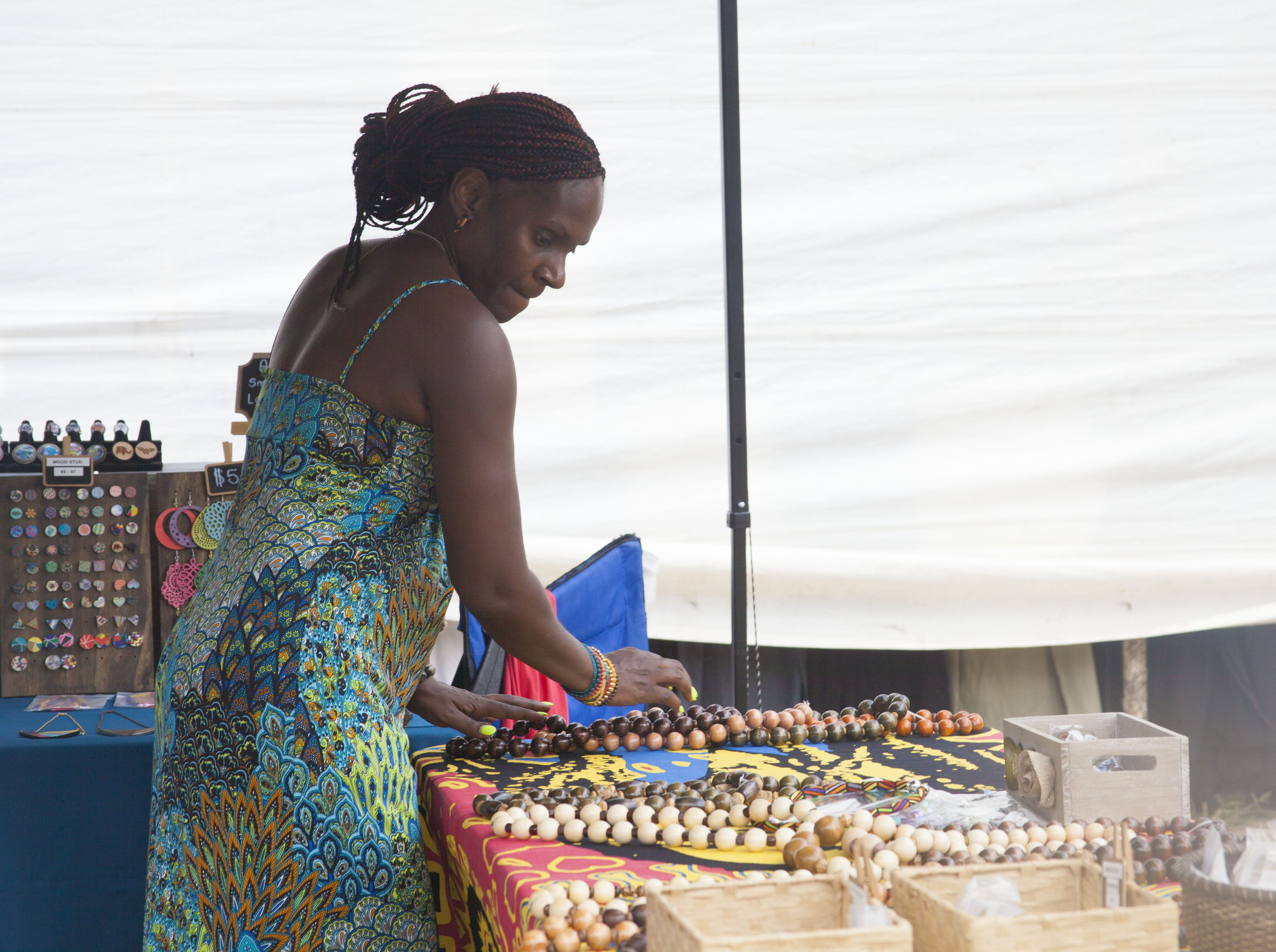 Kim Moore arranges Keenara Shawn's handmade jewelry at the 2018 Goombay Festival at the Roger McGuire Green in Pack Square Park on Sept. 8, 2018.