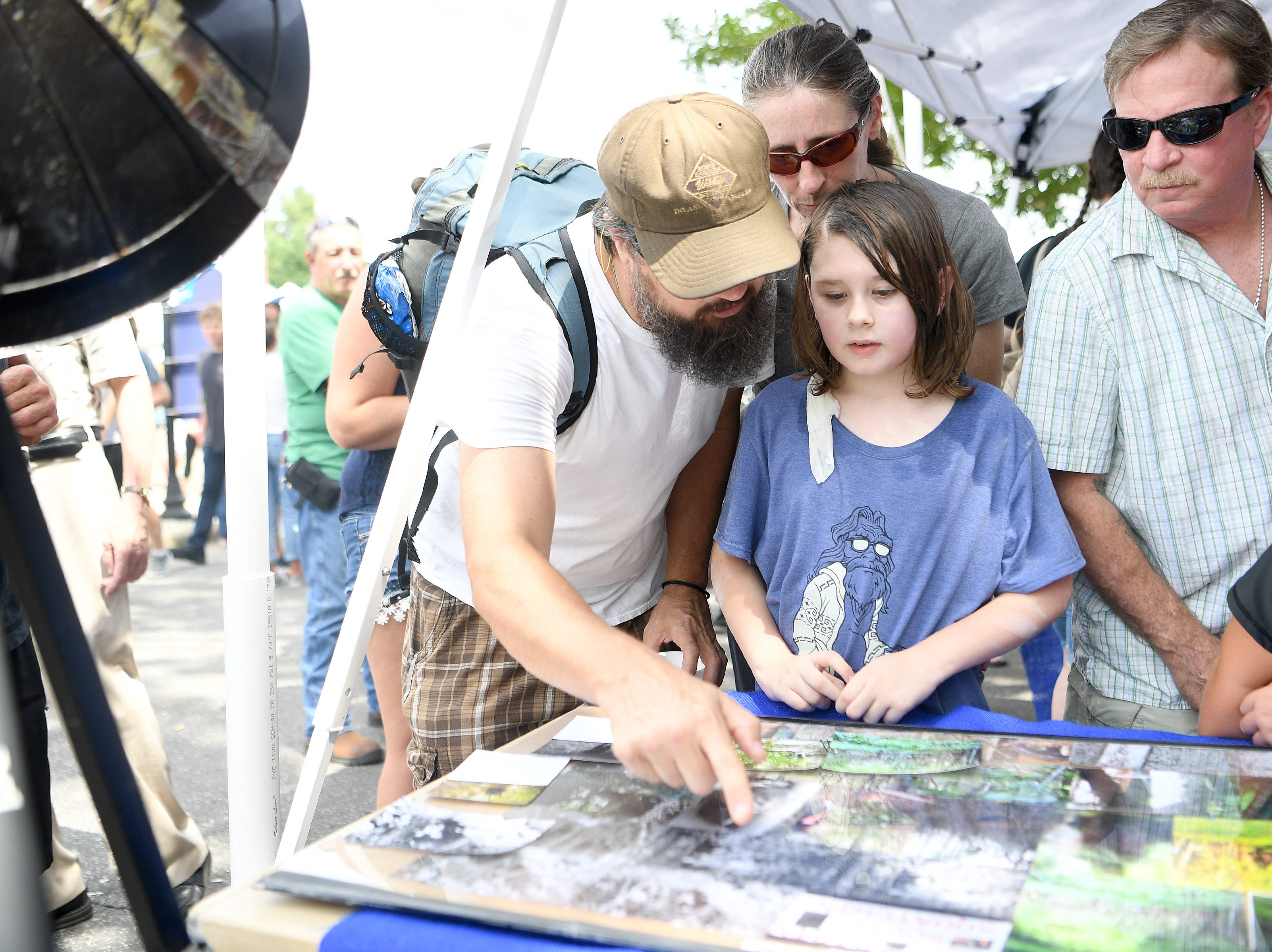 Scott, Susan and Logan, 7, Brown look at photos of Bigfoot at a booth during the first ever WNC Bigfoot Festival in Marion on Sept. 8, 2018.