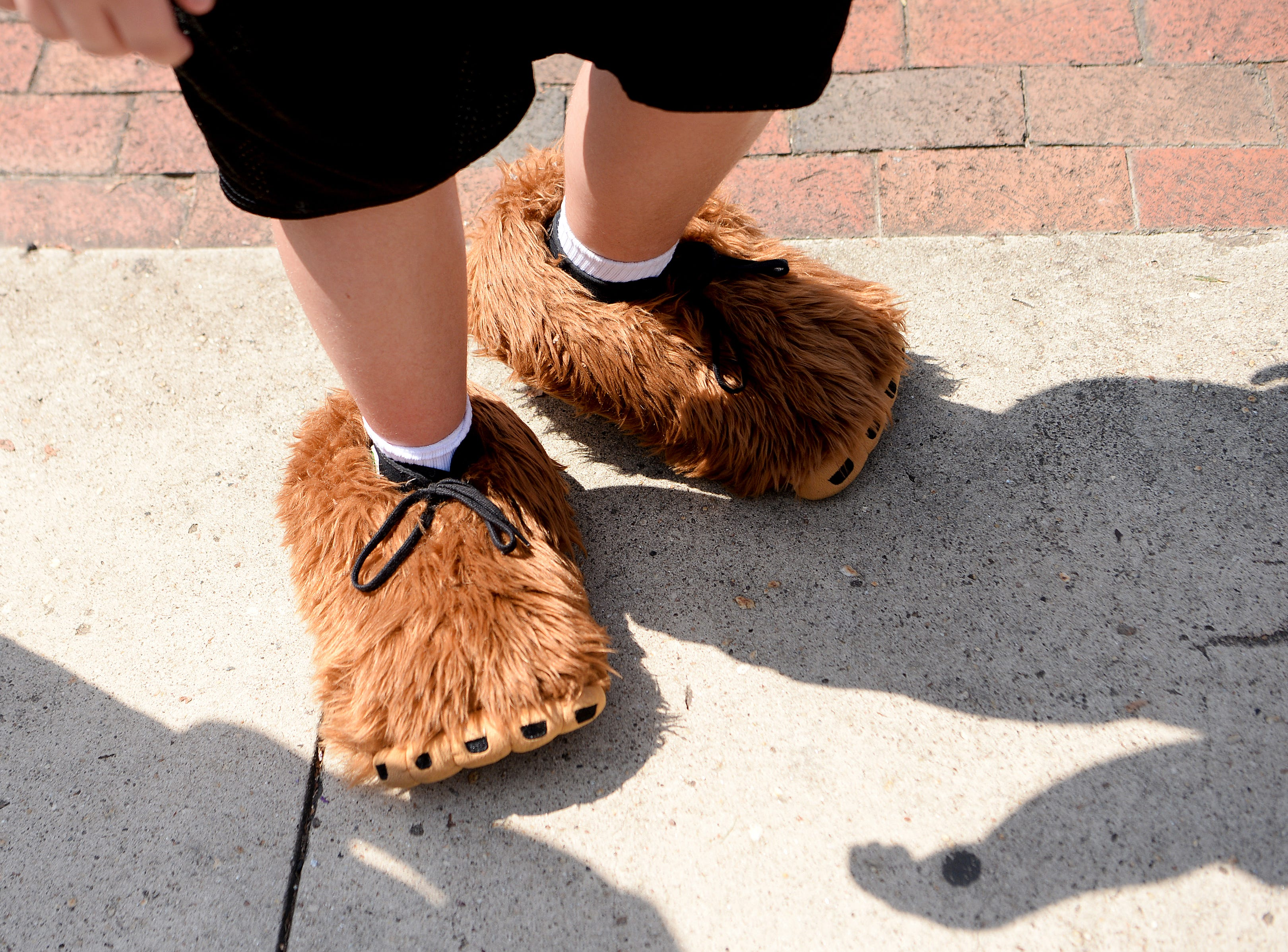 A boy wears ape feet as he walks on Main Street during the first ever WNC Bigfoot Festival in Marion on Sept. 8, 2018.