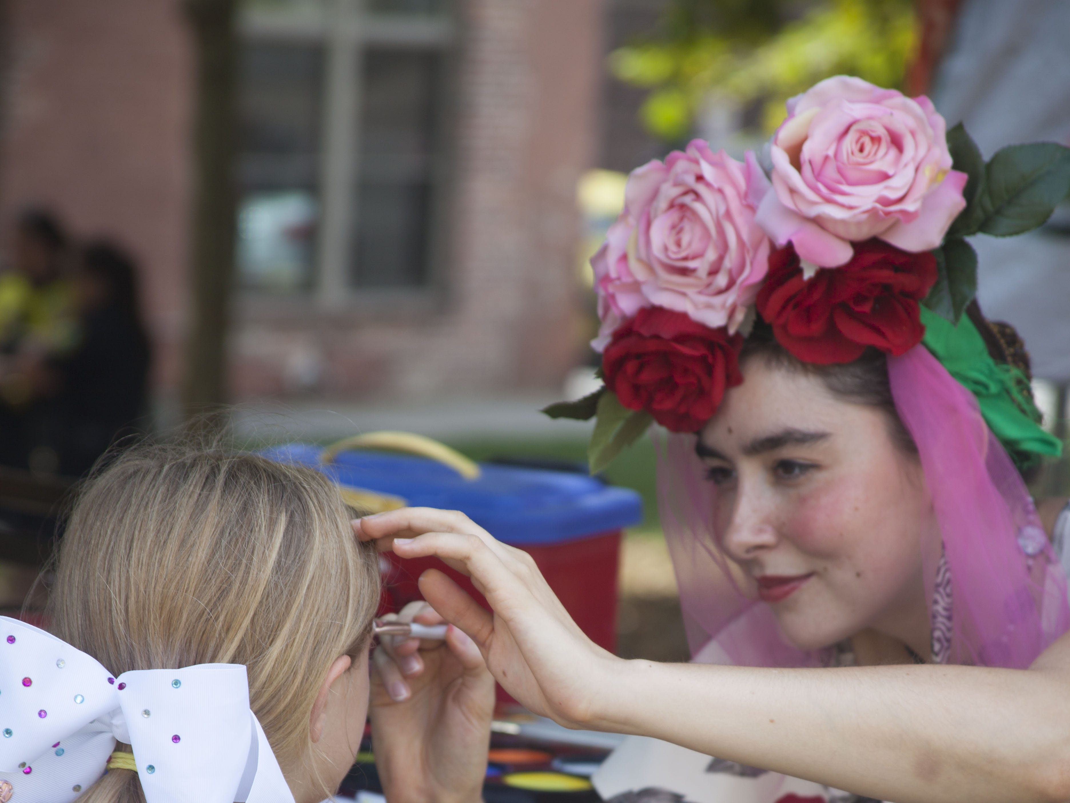 Bonnie Rockwood of The Lady in Red Art paints the face of Madison Gravelle at the 2018 Goombay Festival at the Roger McGuire Green in Pack Square Park on Sept. 8, 2018.