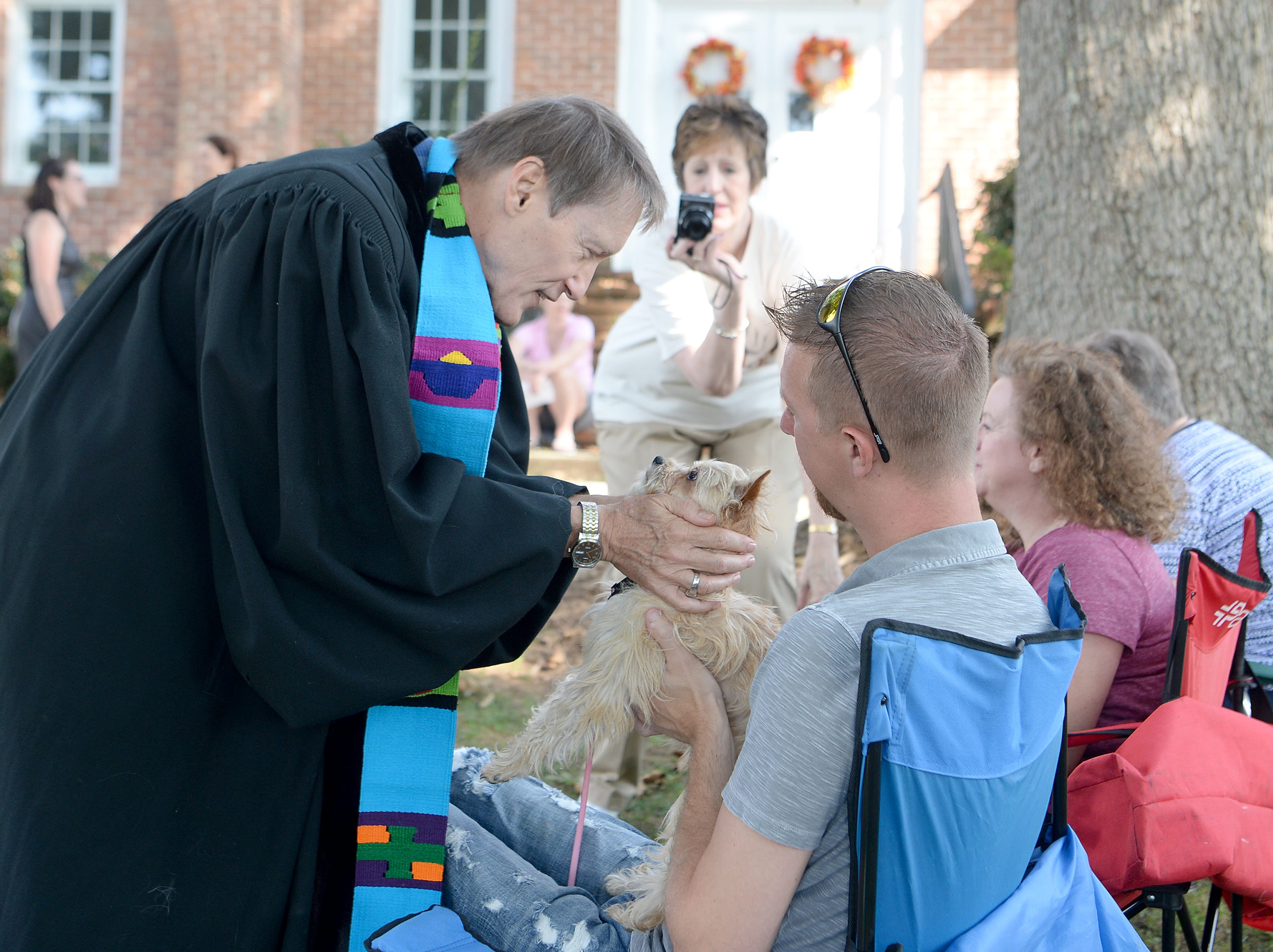Randall Boggs blesses Kevin Fender's dog, Molly, during the 10th Annual Blessing of the Pets at Mills River Presbyterian Church on Sept. 8, 2018.