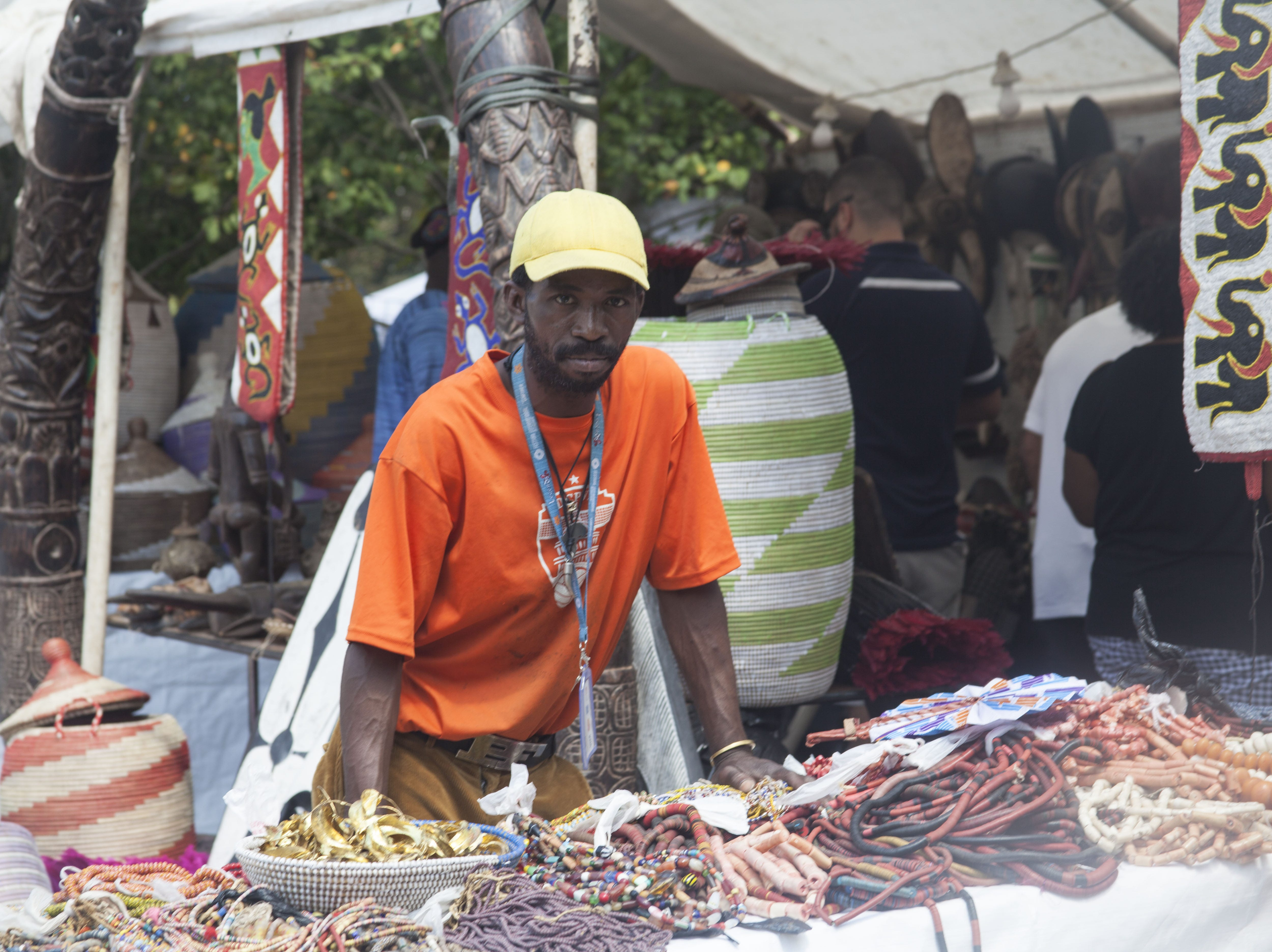 Abdoul Sanogo offers attendees handcrafted items at the 2018 Goombay Festival at the Roger McGuire Green in Pack Square Park on Sept. 8, 2018.