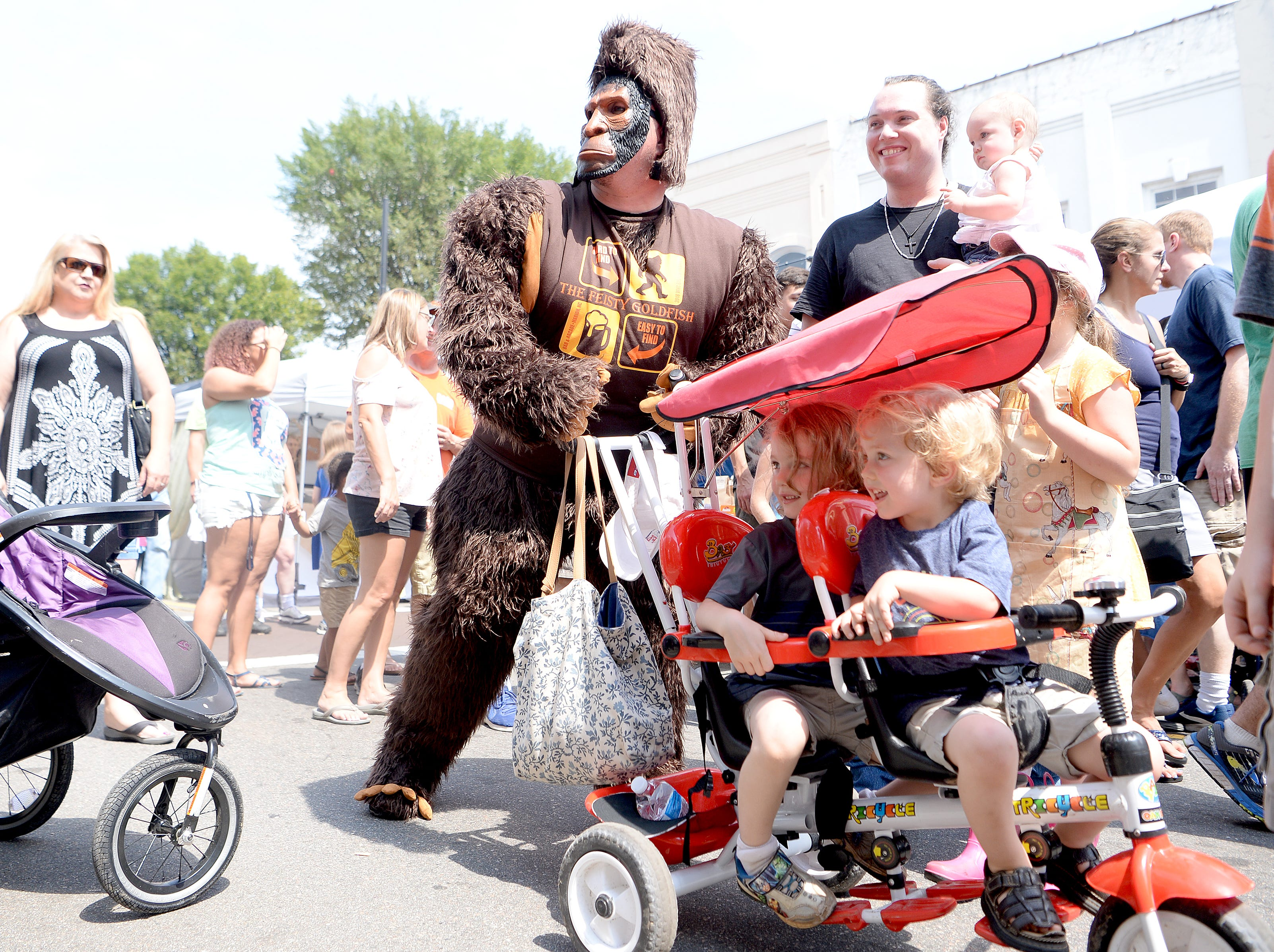 A Bigfoot kidnaps Jacob and Jeremiah Faulkner, 4 and 3 respectively, for a photograph during the first ever WNC Bigfoot Festival in Marion on Sept. 8, 2018.