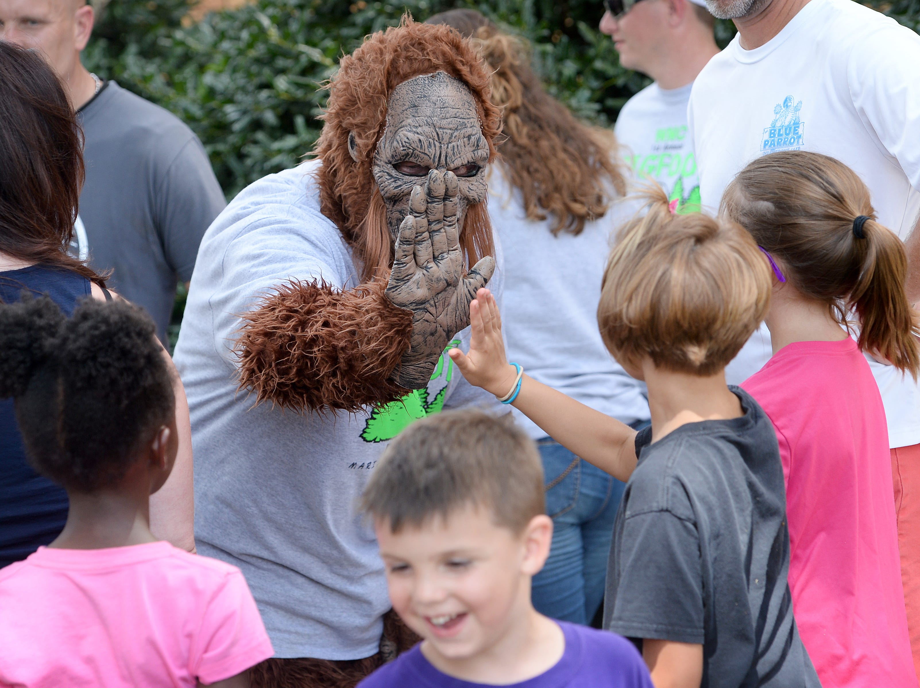 Bigfoot passes out high-fives during the first ever WNC Bigfoot Festival in Marion on Sept. 8, 2018.