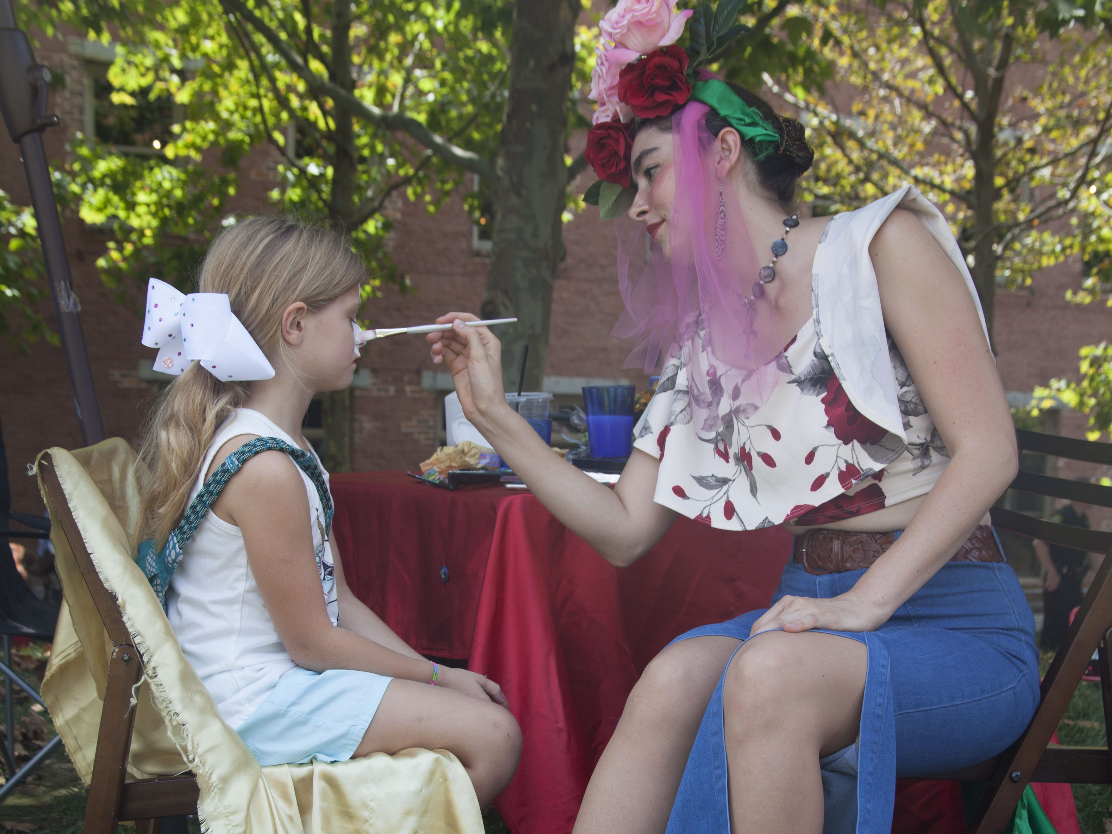 Bonnie Rockwood of The Lady in Red Art paints the face of Madison Gravelle at the 2018 Goombay Festival at the Roger McGuire Green in Pack Square Park on on Sept. 8, 2018.