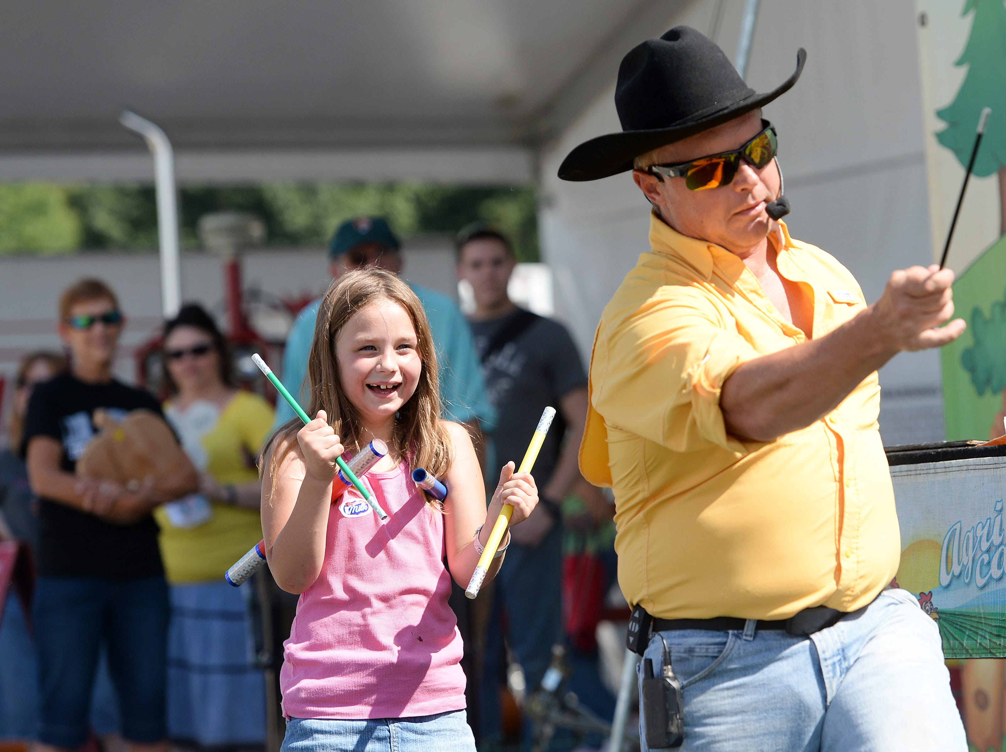 """Adaiah Scilex, 7, laughs as magic wands just keep multiplying in the hands of Brad Matchett, host of Agri Cadabra, a """"magic of agriculture"""" show during the NC Mountain State Fair at the WNC Agricultural Center on Sept. 7, 2018. Matchett is also a hyponist with shows at the fair."""