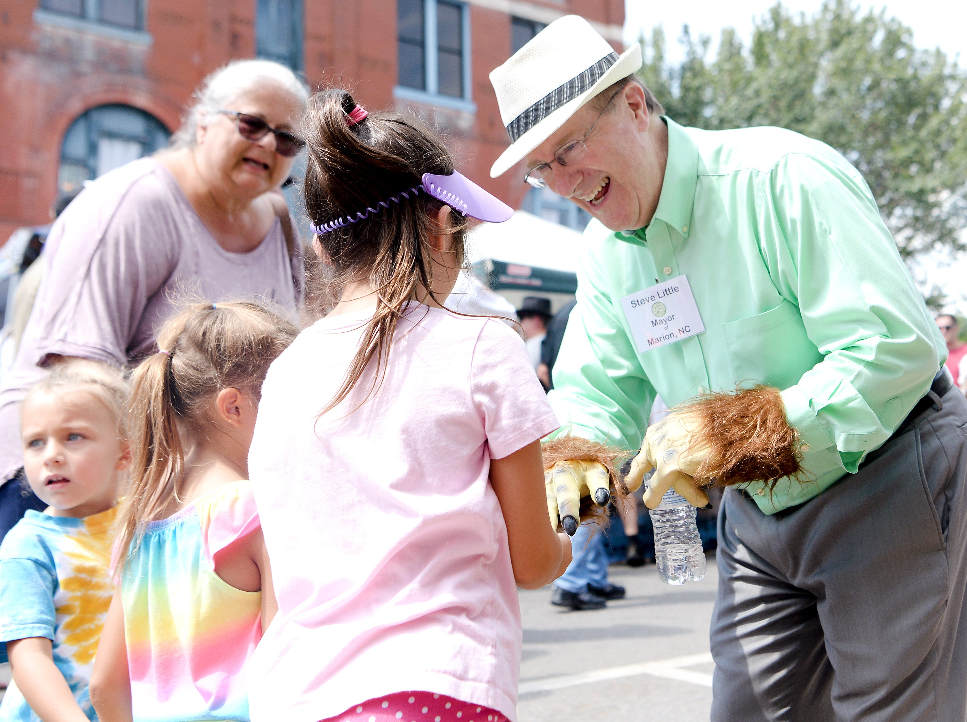 Steve Little, the Mayor of Marion, greets children with his festival-themed hands during the first ever WNC Bigfoot Festival in Marion on Sept. 8, 2018. Little, who estimated the festival received an unplanned for 15,000 visitors said he already has plans to make next year's event better.