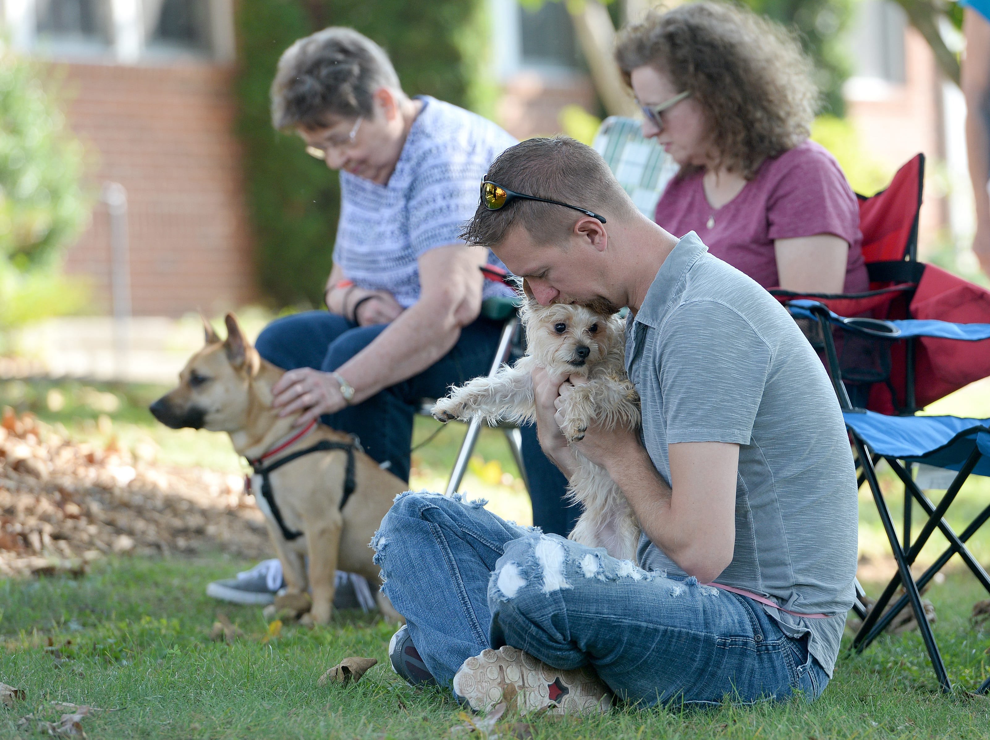 Kevin Fender bows his head in prayer and also gives his dog, Molly, a kiss during the 10th Annual Blessing of the Pets at Mills River Presbyterian Church on Sept. 8, 2018.