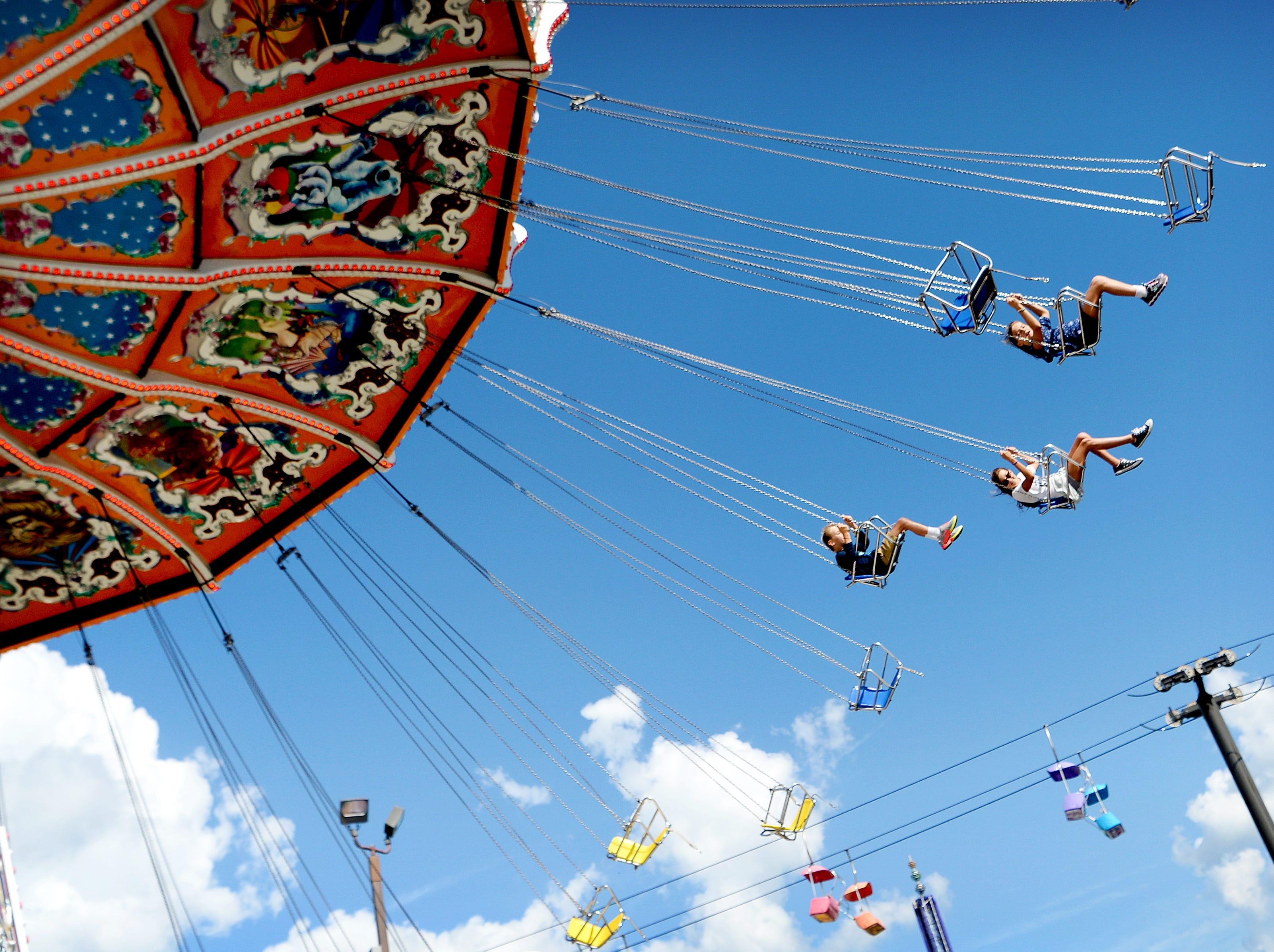 Daniel Thompson, 7, and his sisters Brielle, 11, center, and Lillie, 9, ride the Flying Circus during the NC Mountain State Fair at the WNC Agricultural Center on Sept. 7, 2018.