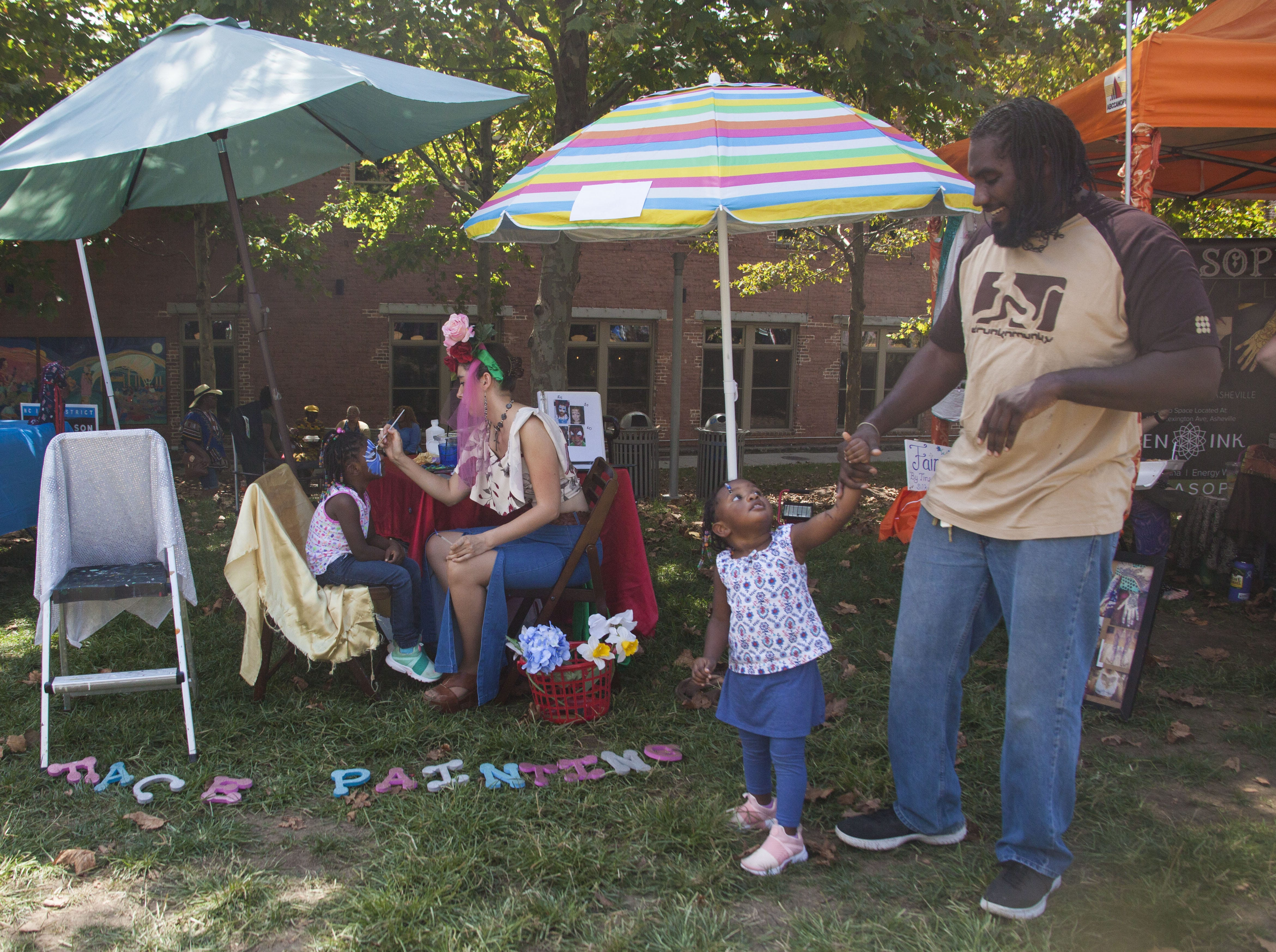 Charles and Penn pose beside the The Lady in Red Art face painting booth at the 2018 Goombay Festival at the Roger McGuire Green in Pack Square Park on Sept. 8, 2018.