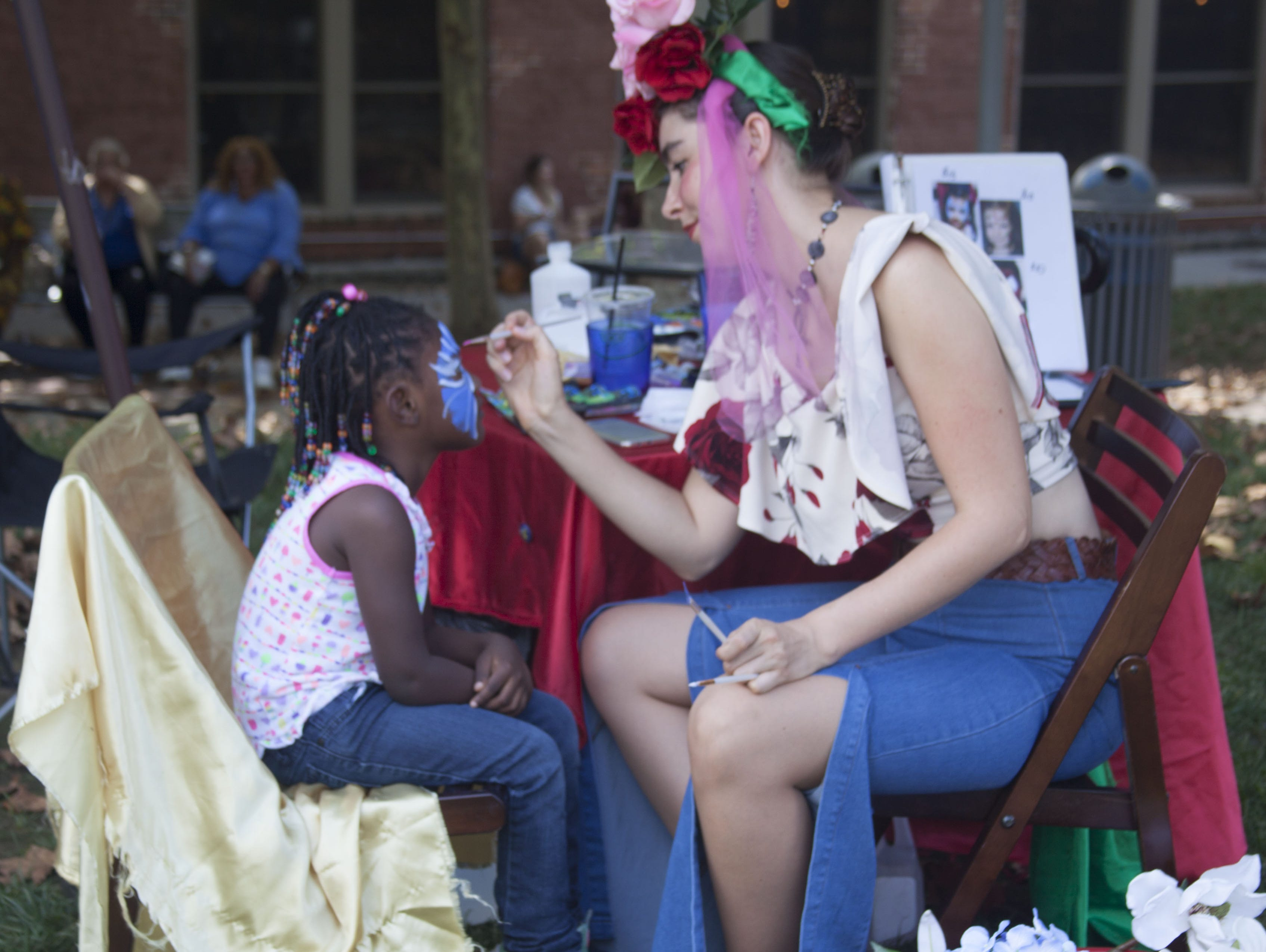 Bonnie Rockwood of The Lady in Red Art paints faces at 2018 Goombay Festival at the Roger McGuire Green in Pack Square Park on Sept. 8, 2018.