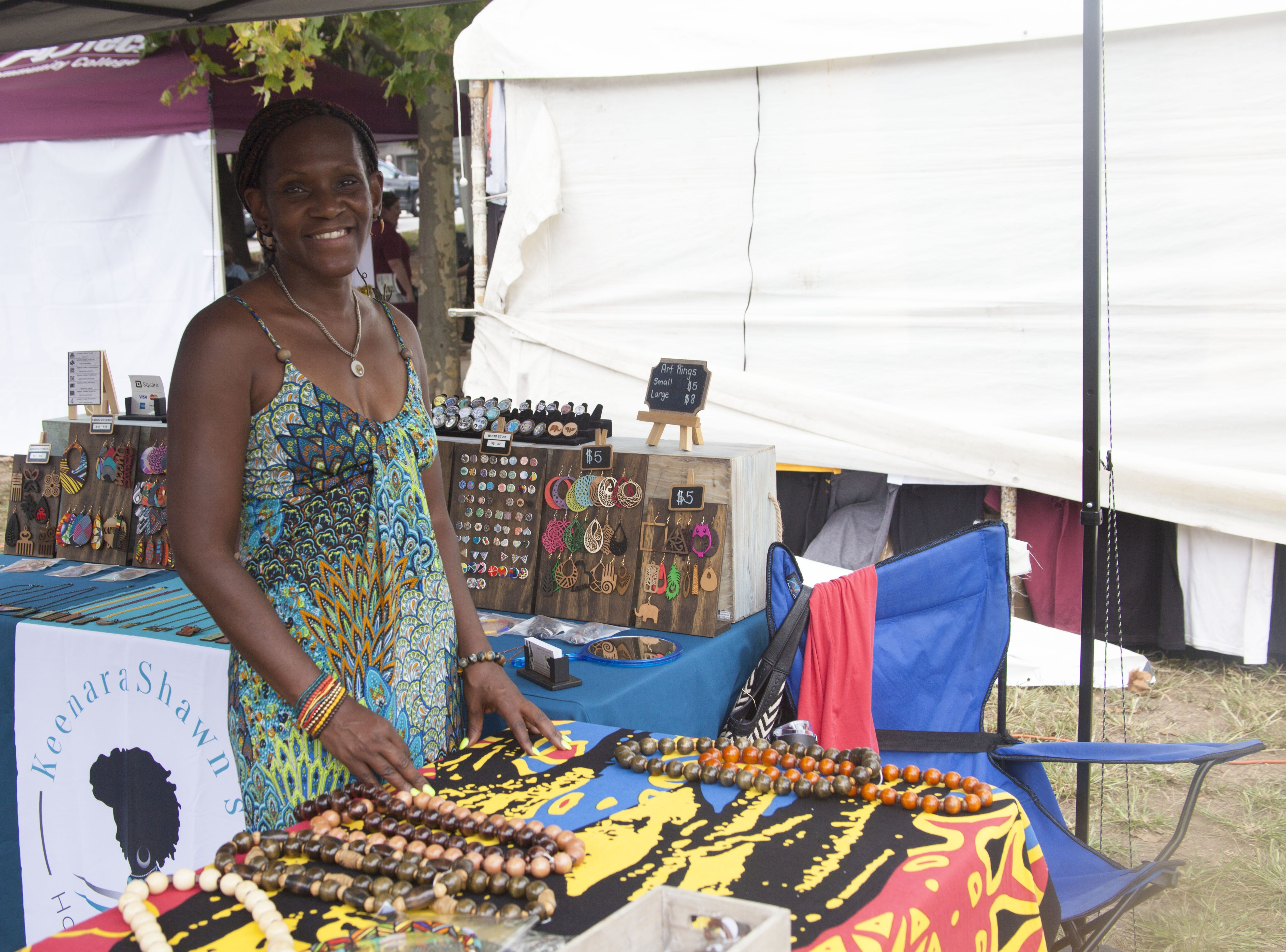 Kim Moore arranges Keenara Shawn's handmade jewelry at the 2018 Goombay Festival at the Roger McGuire Green in Pack Square Park on on Sept. 8, 2018.
