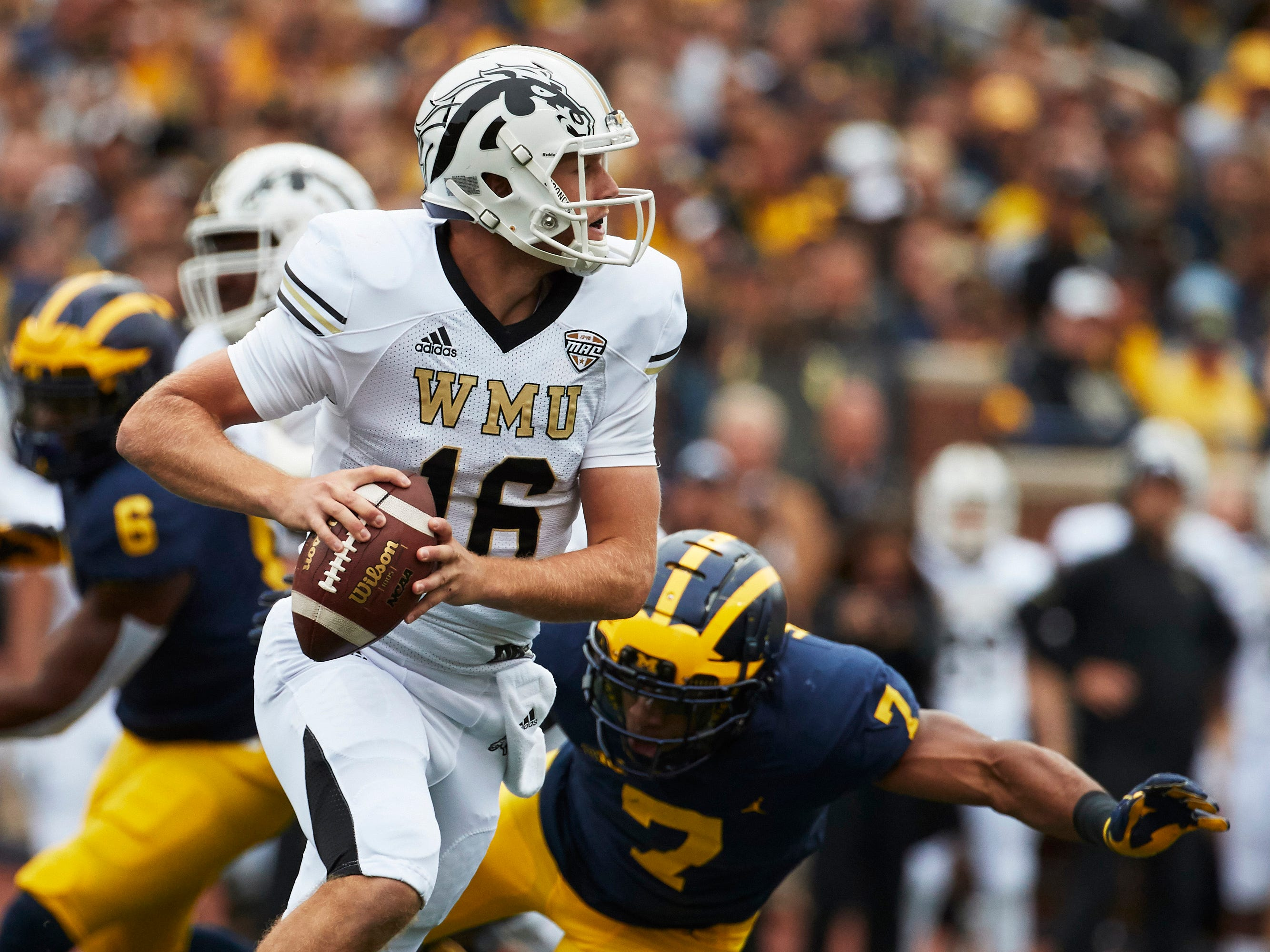 Western Michigan Broncos quarterback Jon Wassink (16) scrambles on Michigan Wolverines linebacker Khaleke Hudson (7) in the first half at Michigan Stadium.