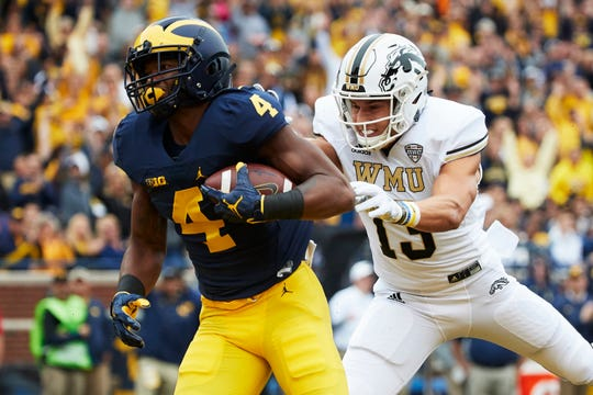 Michigan Wolverines wide receiver Nico Collins (4) scores a touchdown defended by Western Michigan Broncos defensive back Harrison Taylor (13) in the first half at Michigan Stadium