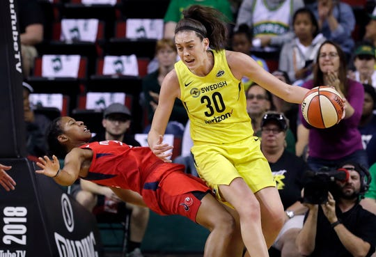Washington Mystics' Ariel Atkins  tumbles backward after fouling Seattle Storm's Breanna Stewart during the first half.