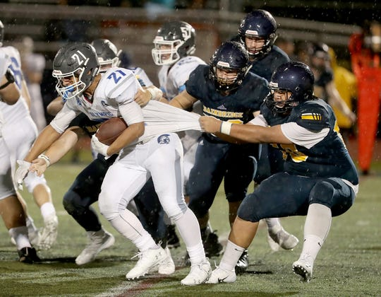 Olympic's Cameron Bailey tries to escape the grasp of several Bainbridge defenders during the Spartans' 28-21 win on Friday.