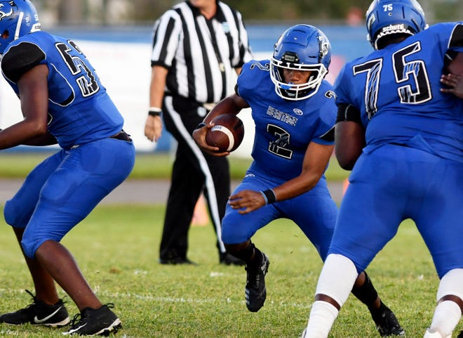 Nigel Scott of Heritage runs through a hole created by his offensive line during Friday's game.