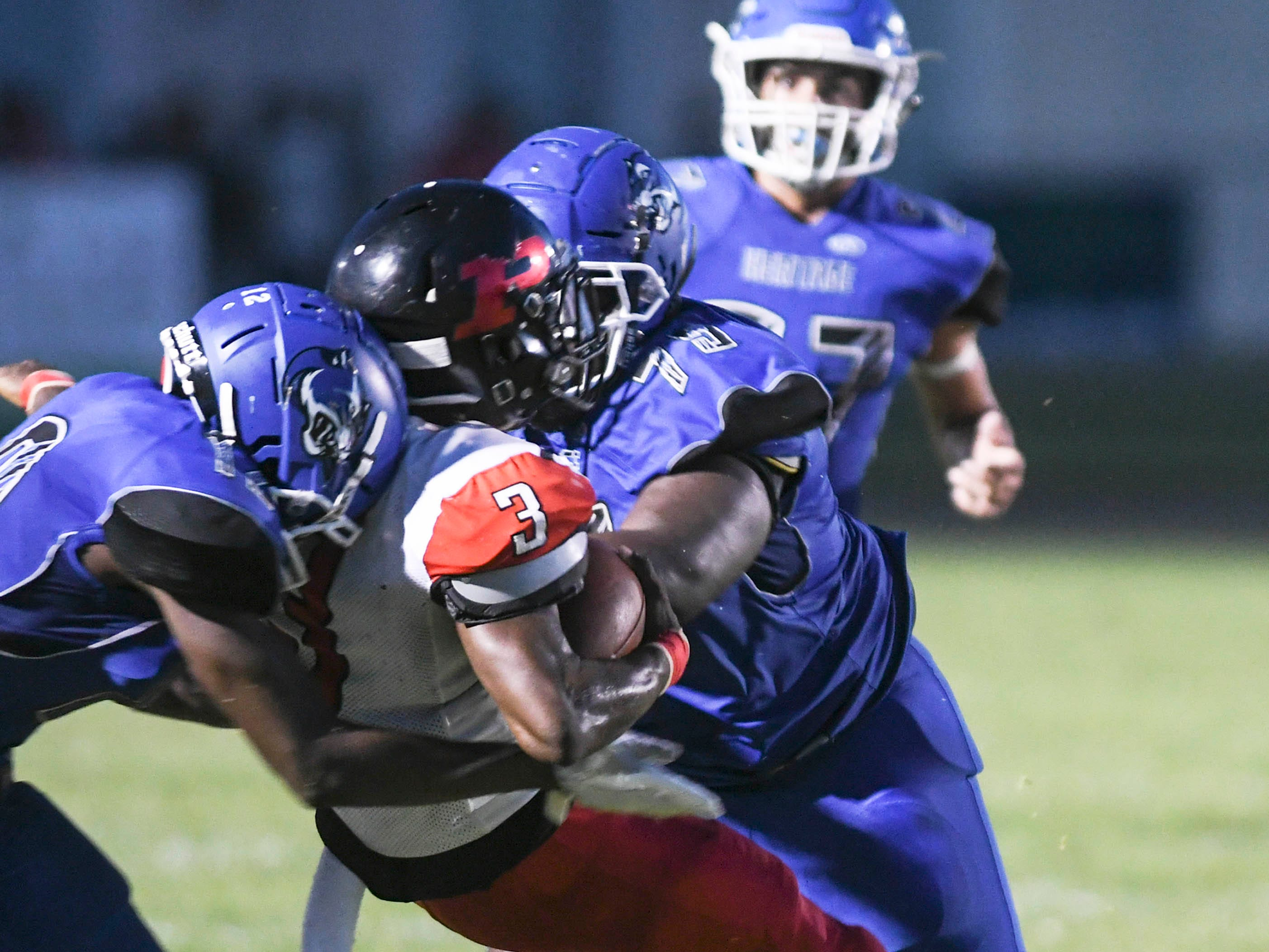 Terrion Howard and Matthew Hall of Heritage take down Palm Bay QB Jaheim Mayes during Friday's game.