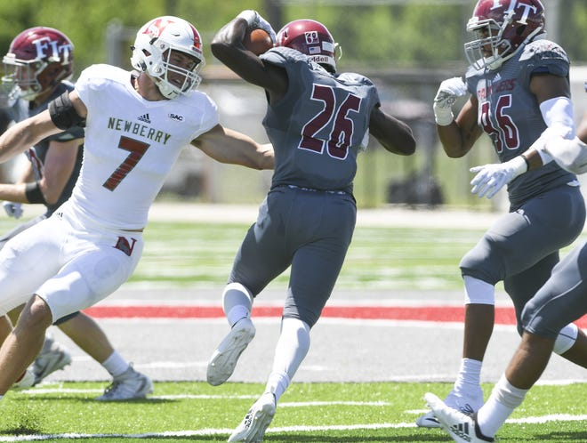 Richard Leveille of Florida Tech (26) runs back a blocked field goal attempt during Saturday's game. Sean Smith of Newberry attempts to make the stop.