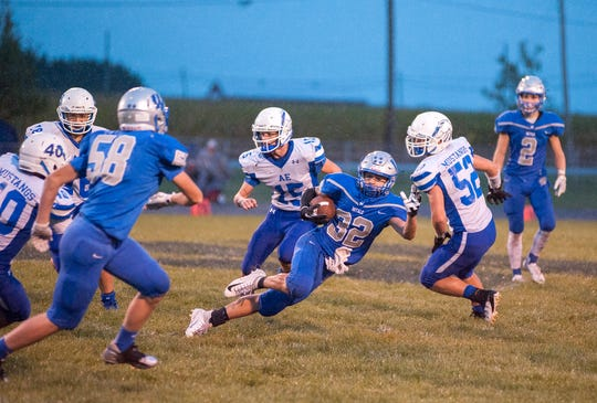 Wynford's Seth Benedict slips on the wet grass while running the ball.
