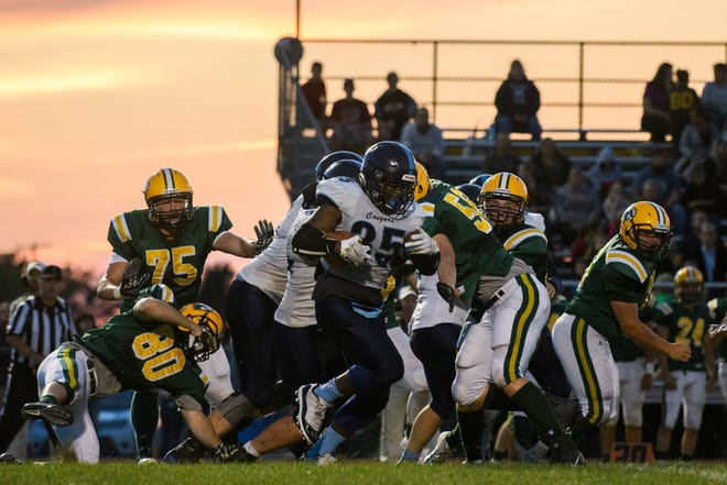 MMU's Jehric Hackney (35) runs with the ball during the football game between the Mount Mansfield Cougars and the BFA St. Albans Bobwhites at BFA High School on Friday night September 7, 2018 in St. Albans.