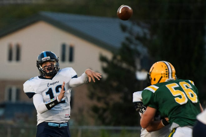 MMU's Asa Carlson (12) passes the ball during the football game between the Mount Mansfield Cougars and the BFA St. Albans Bobwhites at BFA High School on Friday night September 7, 2018 in St. Albans.