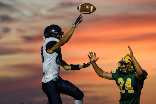 """MMU's Mason Combs (80) passes the ball over BFA""""s Adam Forbes (24) during the football game between the Mount Mansfield Cougars and the BFA St. Albans Bobwhites at BFA High School on Friday night September 7, 2018 in St. Albans."""