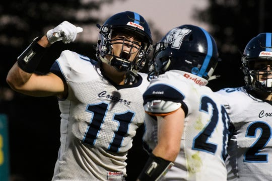 MMU's Harrison Leombruno-Nicholson (11) celebrates an interception and touchdown by MMU's Dylan Davis (28) during the football game between the Mount Mansfield Cougars and the BFA St. Albans Bobwhites at BFA High School on Friday night September 7, 2018 in St. Albans.
