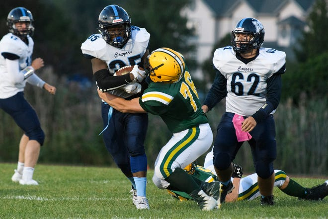MMU's Jehric Hackney (35) is tackled by BFA's Owen Bonnet (76) during the football game between the Mount Mansfield Cougars and the BFA St. Albans Bobwhites at BFA High School on Friday night September 7, 2018 in St. Albans.