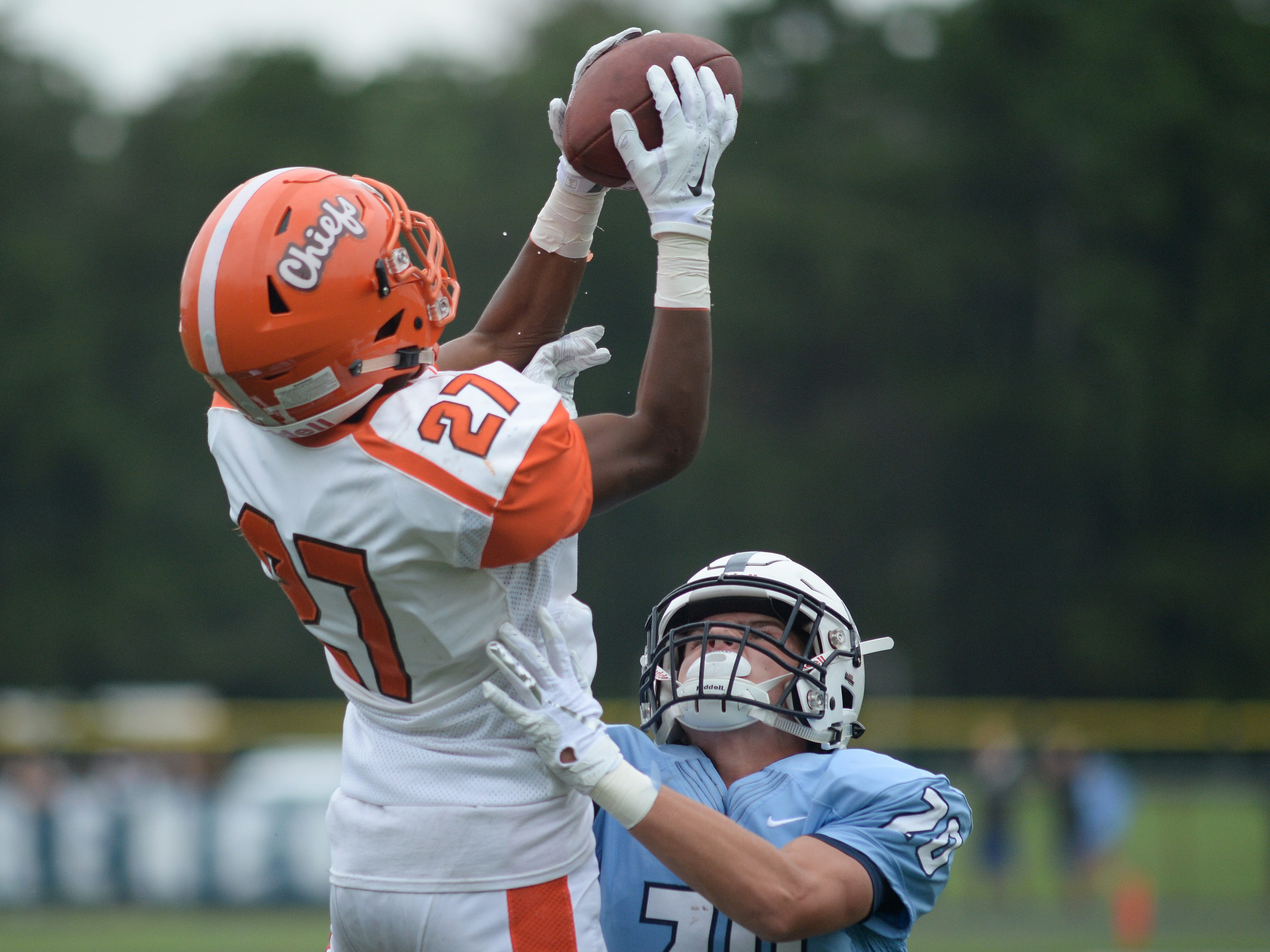 Cherokee's Darnell Hightower catches a touchdown pass with Shawnee's Dom Carbone during Saturday's football game at Shawnee High School,  Sept. 8, 2018.