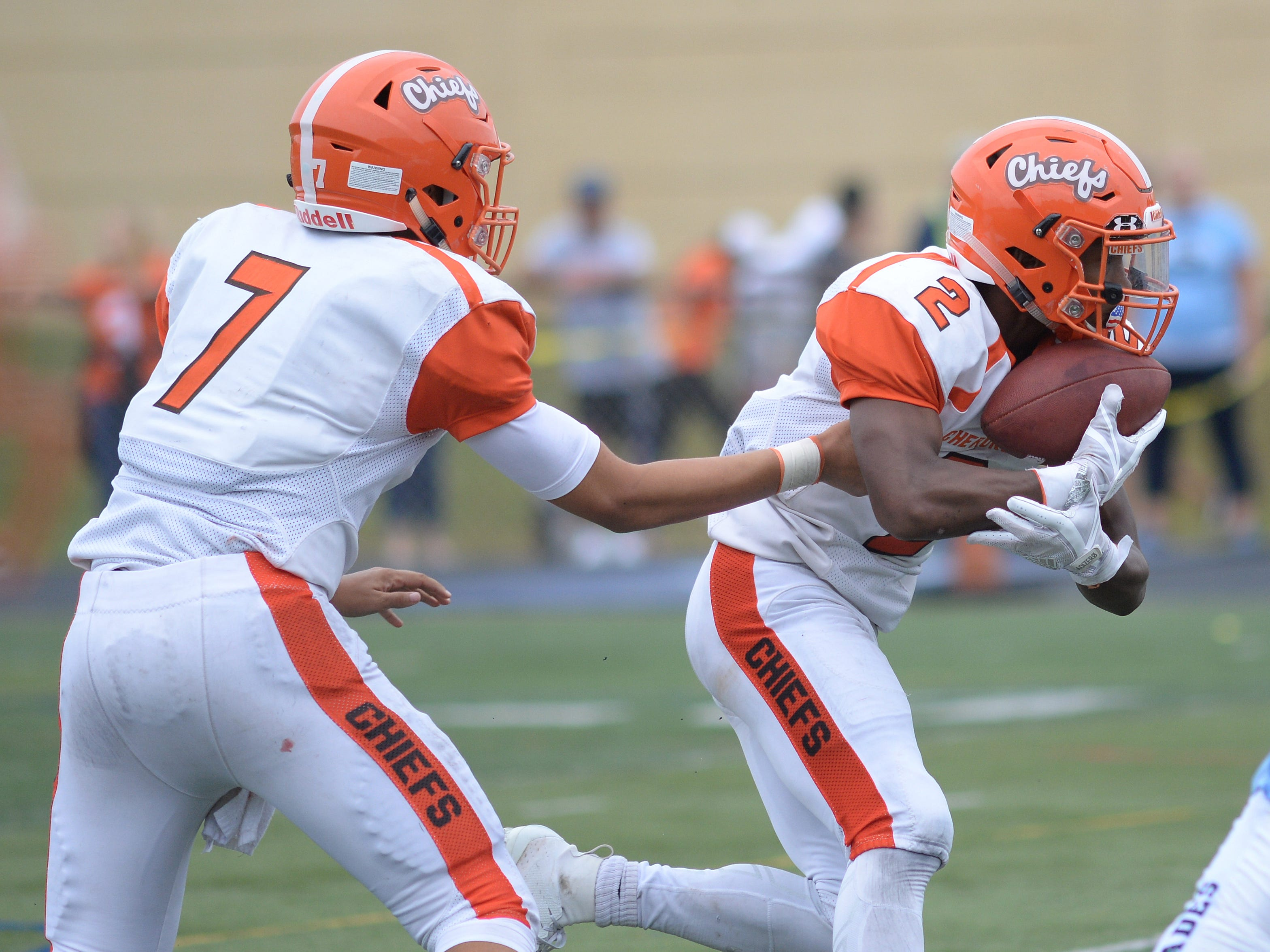 Cherokee's quarter back Aiden Douglas hands off to EJ Bard during Saturday's football game against Shawnee at Shawnee High School,  Sept. 8, 2018.