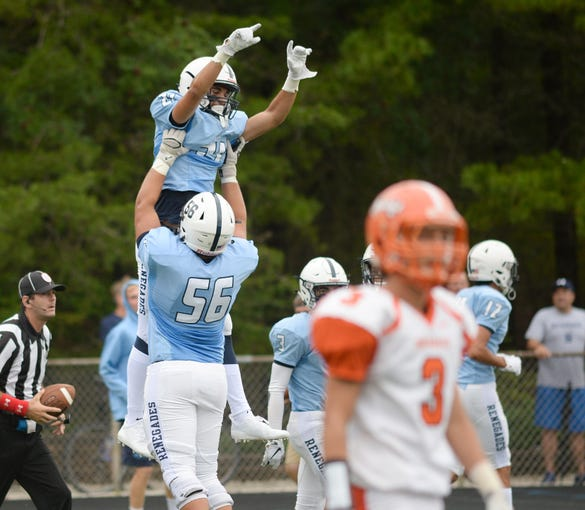 Shawnee's Jon Searcy jumps into the arms of Mike Owsiak after scoring a touchdown during Saturday's football game against Cherokee at Shawnee High School,  Sept. 8, 2018.