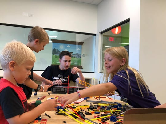 Matt Weinberg, 16, a Code Sensei at Code Ninjas in Cherry Hill, works with the Crossley siblings of Delran: Josh (from left), 5; George, 9; and Audrey, 7, as they construct a K'nex roller coaster.