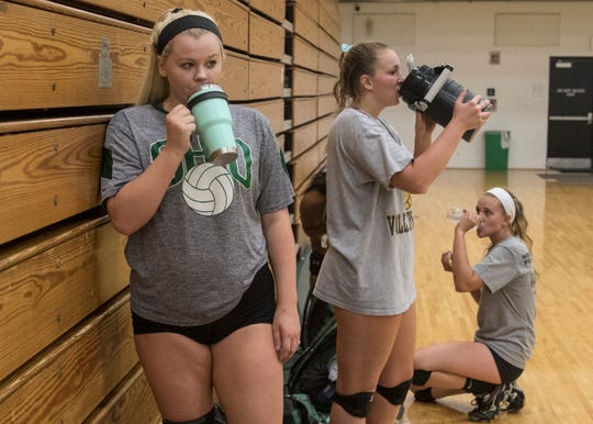 (L-R) Mallorie Williams, Madalyn Eskew, and Hannah Rausch take a moment to rest and hydrate during volleyball practice Wednesday evening at Ohio University-Chillicothe.
