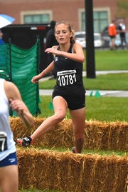 Maddie Walker of West Clermont hurdles the hay bales while running  at the 44th Annual Mason Cross Country Invitational, Sept. 8, 2018.
