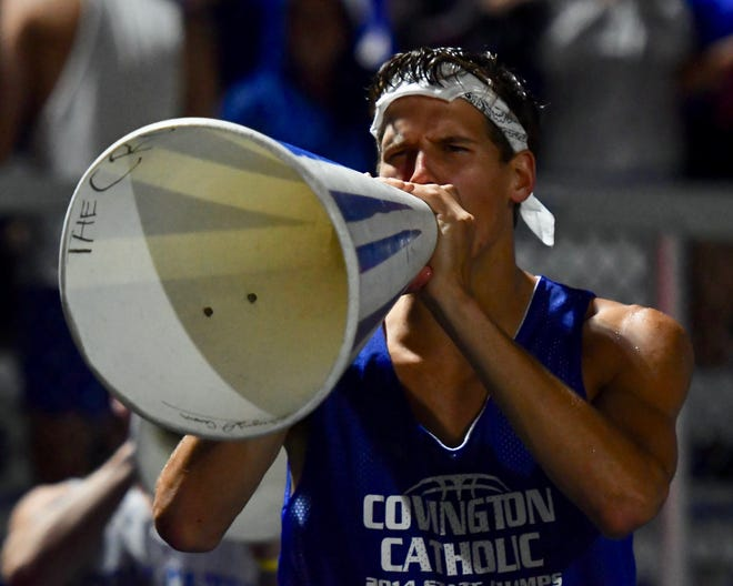 A Covington Catholic student cheers on the Colonels in a rainstorm Friday, Sept. 7, 2018 at Covington Catholic High School