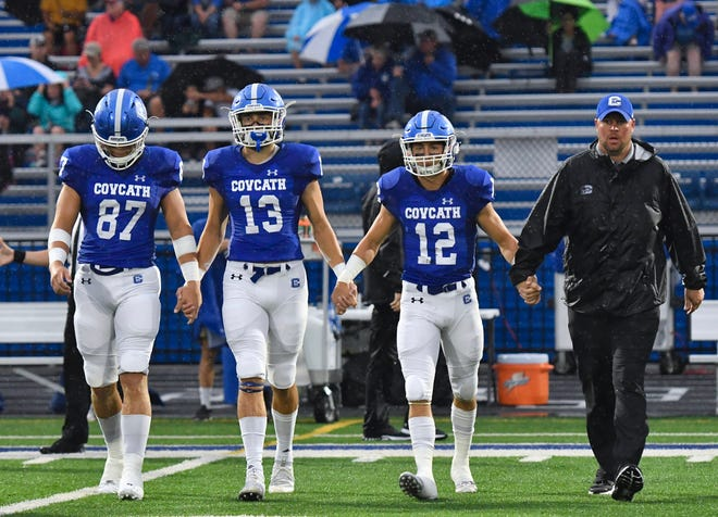 The Covington Catholic captains, from left, Michael Mayer, Jack Coldiron and Tyler Reusch, join their coach to take the field for the coin toss before their game against Kings Friday, Sept. 7, 2018 at Covington Catholic High School