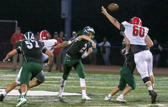 Ridge QB Wesley Hudkins throws a pass under pressure by Hunterdon Central defenders in Basking Ridge on September 7, 2018. (Photo by Keith Muccilli, Correspondent)