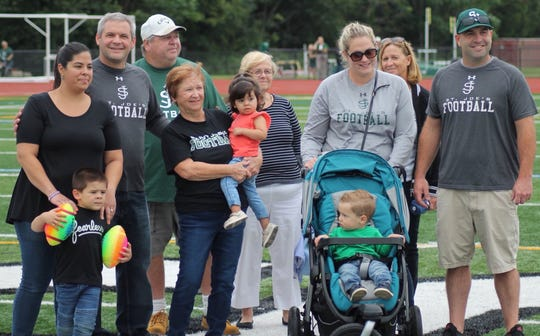 The family of Michael Cleary poses for a photo during a pregame ceremony in honor of the legendary coach.
