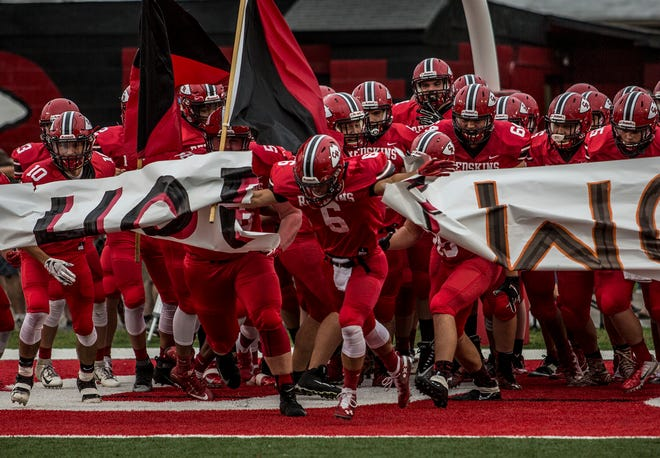 Coshocton's football team bursts through a banner prior to its game against visiting Ridgewood in 2019 at Stewart Field. The local teams got the clear to play football from Gov. Mike DeWine on Tuesday, even as Ohio State and other Big Ten college programs will be sitting at home.