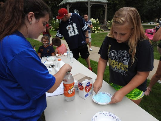Emilee Waddell helps Raelynn Wright, 11, of Coshocton make slime during a National Recovery Month event at the Coshocton Court Square held by Coshocton Behavioral Health Choices.