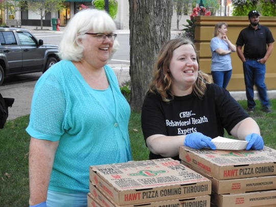 Beth Cormack, Executive Director of Coshocton Behavioral Health Choices, and Jeannette Hall, director of prevention services and senior counselor, serve pizza and watch a limbo contest during a National Recovery Month event on the Coshocton Court Square.