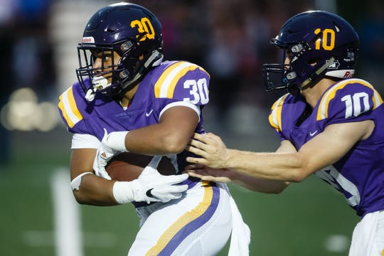 Johnston's Nuutele Davis (30) takes a handoff from Johnston's Andrew Nord (10) during their football game against Dowling Catholic at Johnston on Friday, Sept. 7, 2018 in Johnston.