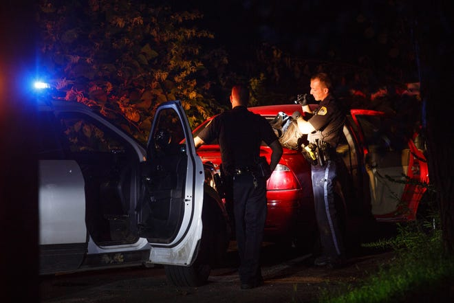 Des Moines officers search a car at Franklin Avenue and 24th Street on Friday, Sept. 7, 2018 after police were involved in a chase.