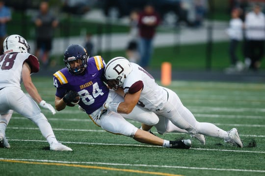 Johnston's Peyton Williams (84) is tackled by Dowling Catholic's Levi Hummel (48) during their football game at Johnston on Friday, Sept. 7, 2018 in Johnston.