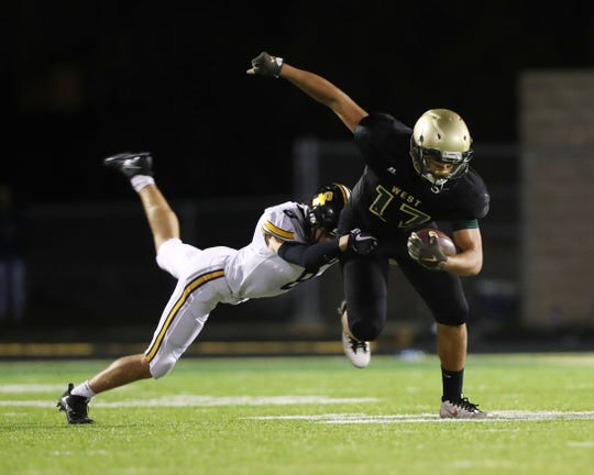 Iowa City West Trojans Jalen Gaudet (17) catches a pass in front of Southeast Polk Rams TJ Armstrong (8) Friday, Sept. 7, 2018, in Iowa City, Iowa.