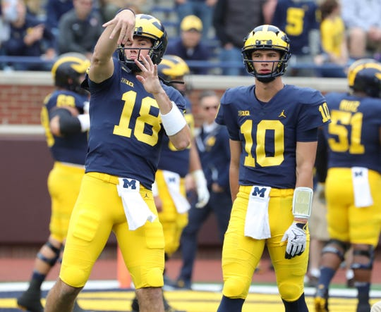Michigan quarterbacks Brandon Peters, left, and Dylan McCaffrey warm up before action against Western Michigan  on Saturday, Sept. 8, 2018, at Michigan Stadium.